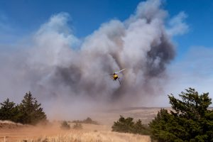 A helicopter flying over the Rhea Wildfire